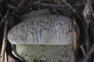 その岩の下に、何やら文様の書か...