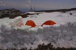 テント場。テントの周りに雪のブ...