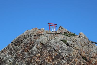 夫婦石の上に鳥居が立っている。...